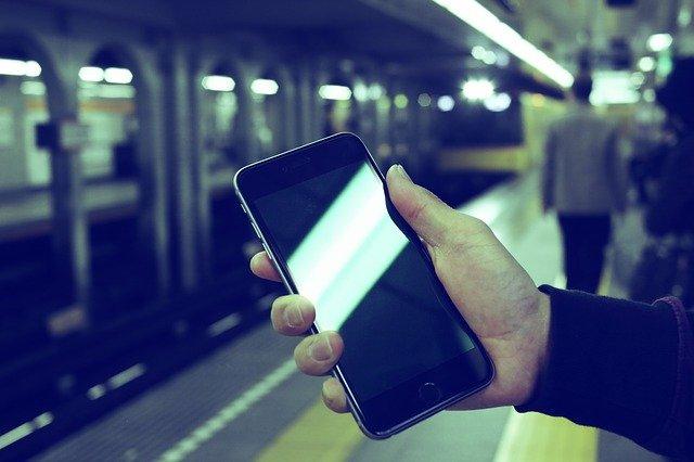 駅のホームでスマートフォンをいじる